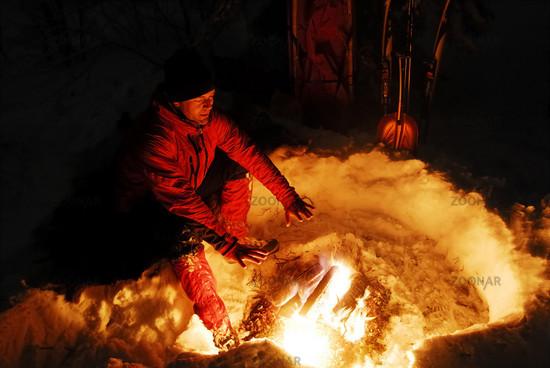 Mann waermt sich die Haende am Lagerfeuer