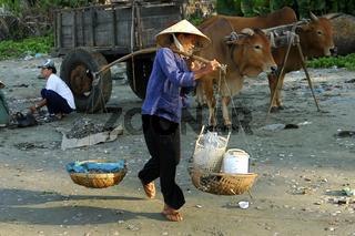 Frau transportiert in Tragekörben ihre Einkäufe