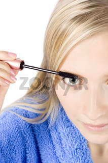 closeup of young woman's face putting mascara