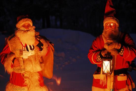 zwei Weihnachtsmaenner am Lagerfeuer, Gaellivare