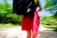 Woman in red shorts and a black backpack out walking in the middle of the nature.