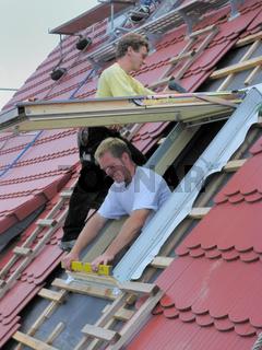 zwei Dachdecker beim Dachfenstereinbau