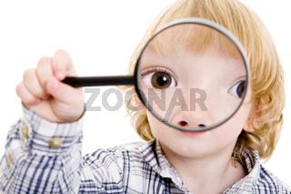 Junge blickt durch Lupe