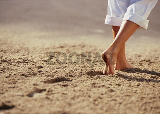 Frauenbeine im Sand