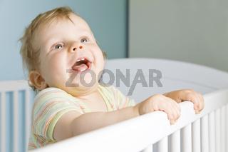 Lachender Junge im Kinderbett
