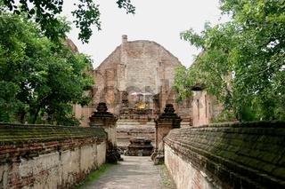 Pfad durch Khmer Ruinen mit Buddha Schrein im Hint