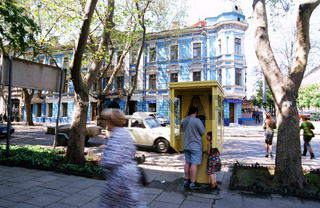 Ukraine, Odessa, man and child at public phone booth