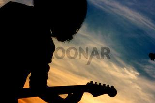 Gitarre spielen im Sonnenuntergang