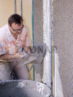 Bauarbeiter beim Fassadenputz in Kellenwurftechnik