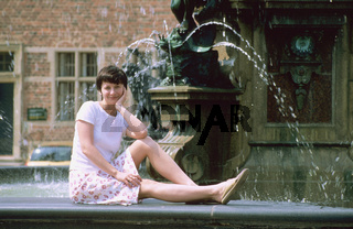 Denmark, Hillerod, Fredericksburg castle, young woman sitting in front of fountain. portrait