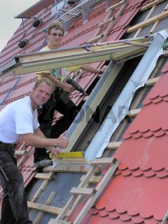 zwei frohe Dachdecker beim Dachfenstereinbau