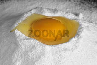 Ei in einer Mulde aus Mehl