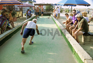 People playing petanque (boule) on Rimini beach Italy, Man playing bocce outdoors