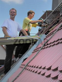 zwei lustige Dachdecker beim Dachfenstereinbau