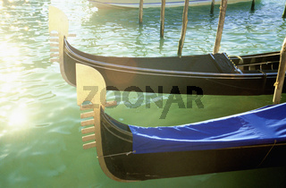 Gondolas in sun on water surface Canale Grande Grand Canal, Carved prows of gondolas moored by canal, Venice, Italy