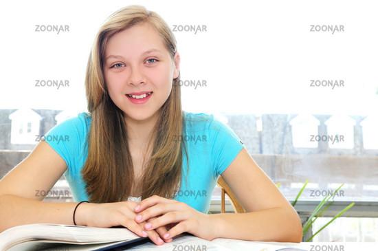 Happy teenage girl studying