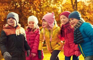 group of happy children having fun in autumn park