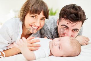 Glückliche Eltern zusammen mit ihrem Baby