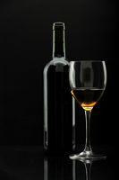 bottle of wine and wineglass over black,