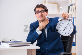Businessman employee in urgency and deadline concept with alarm
