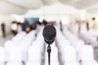 Microphone in focus, empty conference room in the background