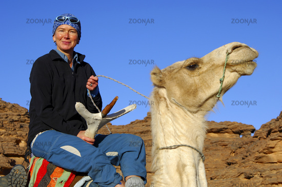 Touristin reitet stolz auf einem Reitkamel
