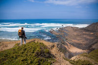 Tourist with backpack on the edge of a beautiful cliff near the ocean Portugal Algarve