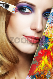 Young woman painter with color palette and paint brush
