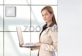 Attractive businesswoman using laptop smiling