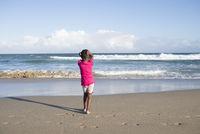 Little girl alone on beach.