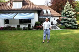 Freundlicher Senior vor seinem Haus im Garten -