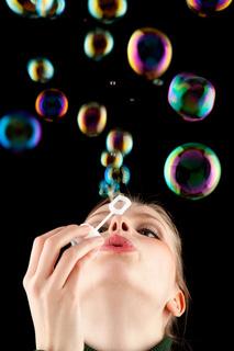 schönes blondes Mädchen macht bunte Seifenblasen