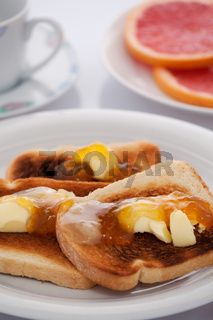 French toast and sliced orange on white tablecloth