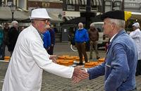 Käsehändler und Bauer feilschen um den Preis für Gouda Käse per Handschlag, Gouda, Niederlande