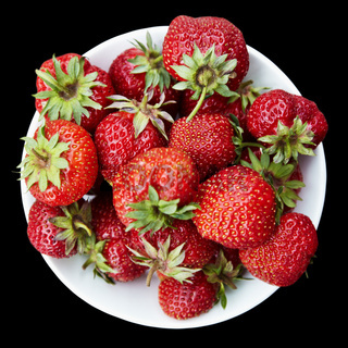 Strawberries on plate on black background