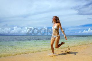 Young woman running on the beach on Taveuni Island, Fiji.
