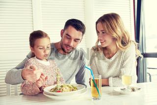 happy family having dinner at restaurant or cafe