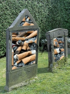 Zwei Grabsteine unterlegt mit Zigarettenkippen