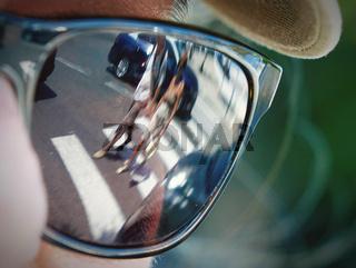 Sonnenbrille spiegelt Fußgänger über Zebrastreifen gehenend