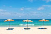 Three empty sunbeds and beach parasol sunshades on sand beach
