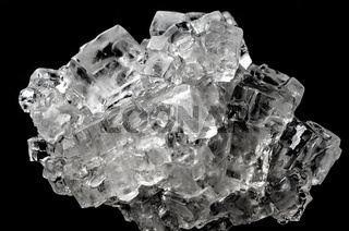 Cubic salt crystal aggregate against black background