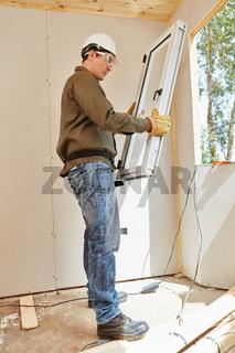 Fenstermonteur baut ein Fenster ein