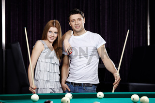 The young attractive couple plays billiards