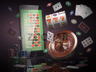 Online casino concept. Mobile phone, roulette with casino chips, slot machine and cards.