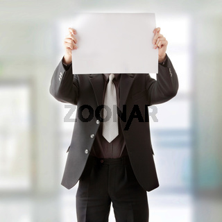 Young businessman holds blank signs.