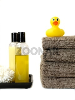 A stack of bath towels and a rubber duck isolated against a white background