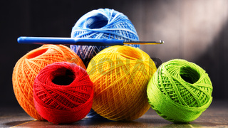 Colorful yarn for crocheting and hook on wooden table.