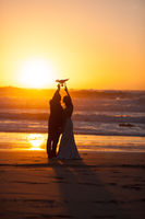 The bride and groom hold drone at sunset near ocean