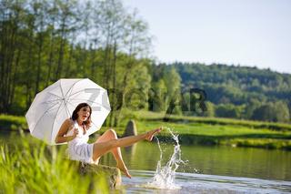 Happy romantic woman sitting by lake splashing water