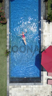 The young beautiful woman swims in the pool
